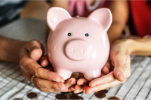 Two pair of hands holding a piggy bank