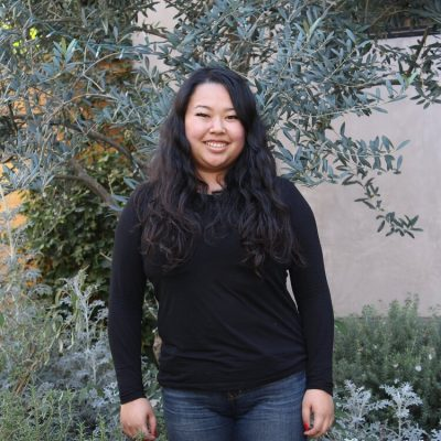 Headshot of Sharon Lim wearing a black long-sleeve shirt and jeans. Her arms are at her side and she faces the camera directly with a smile.