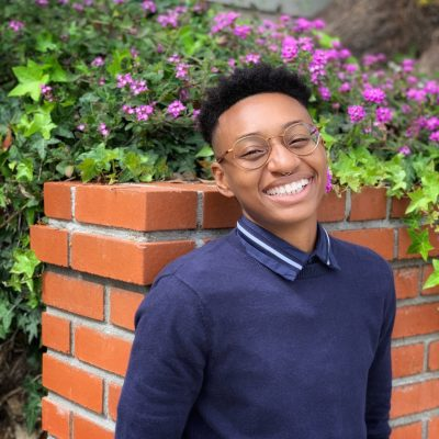 Headshot of Em Jackson leaning their back against a brick wall, wearing a blue sweater over a blue button up and gold rounded glasses. Their head is tilted slightly back as they smile wide and face the camera.