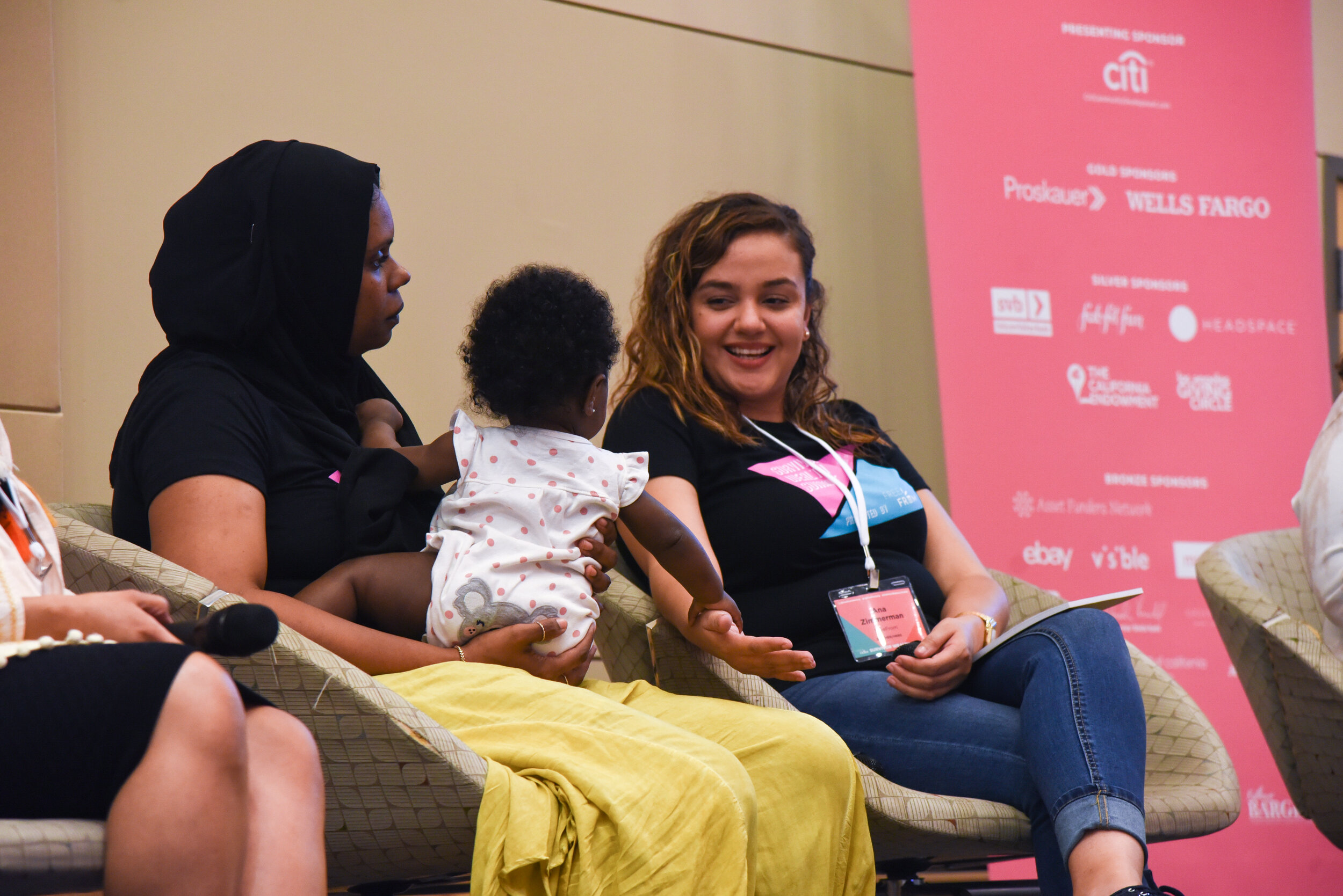Two adults sitting on a stage, one holding a baby in their lap. The adult with the baby in their lap looks out of frame intently while the other adult smiles and interacts with the baby.
