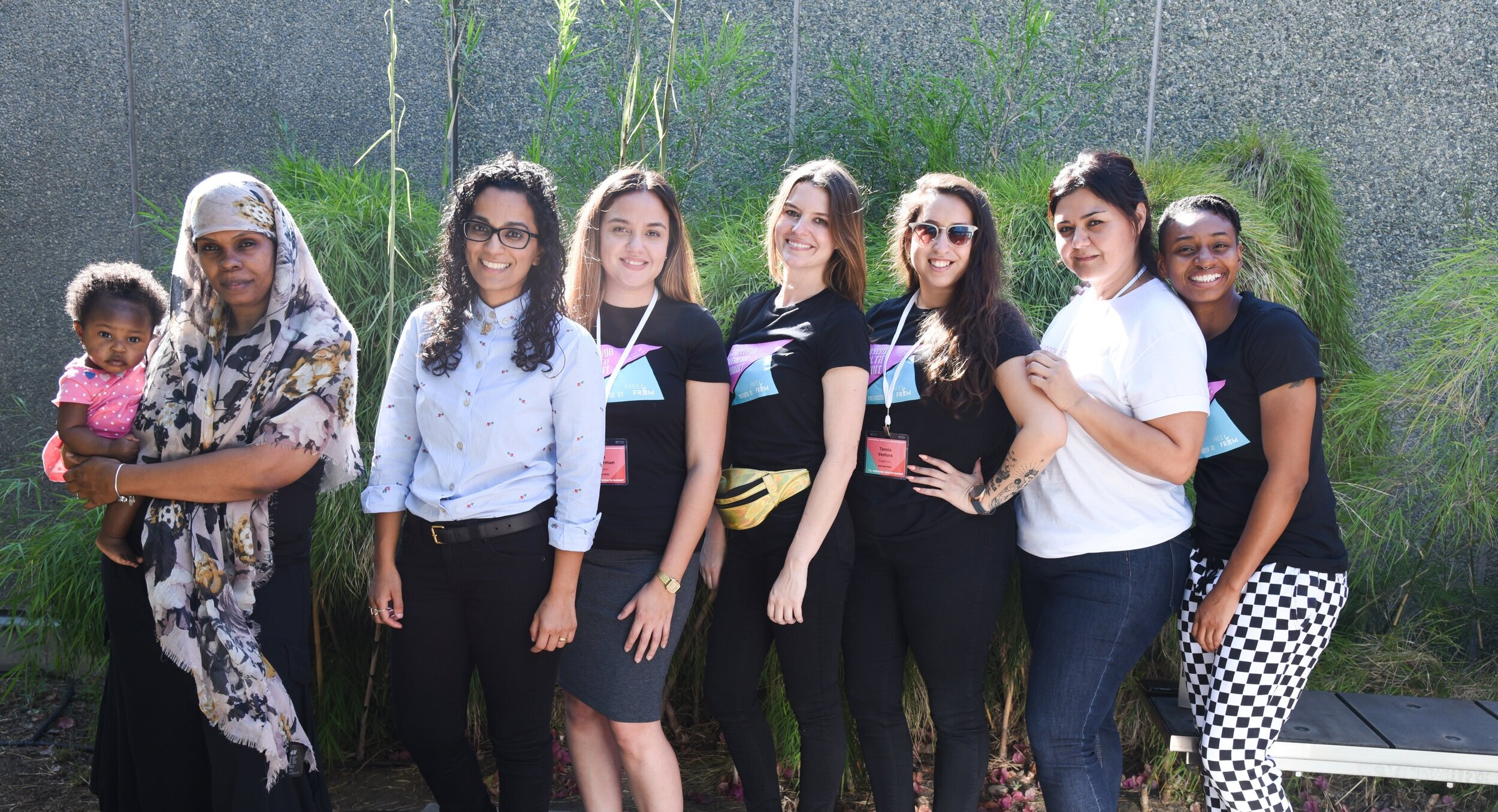 The FreeFrom team members standing close together in front of some green bushes, smiling at the camera