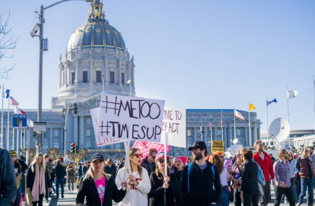 """Large crowd of protesters, holding up signs that reading: """"#MeToo"""" and """"#TimesUp"""" in front of the United States Capitol building."""