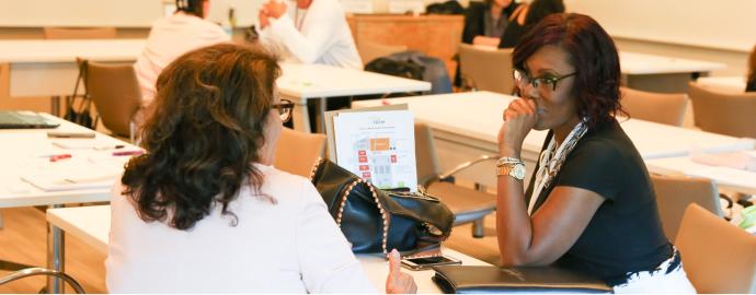 Two people talking across a desk