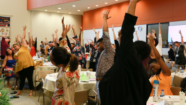 A group of people standing around large tables, stretching their arms upwards in a group excerise