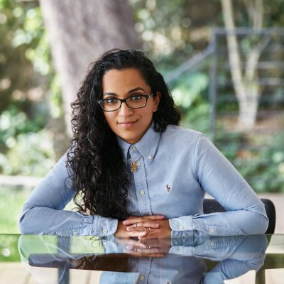 Headshot of Sonya Passi wearing a blue long-sleeve button up and black rectangular glasses, her forearms leaning against the glass table where she is seated. Her lips turned upward in a smile, her eyebrows slightly raised.